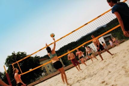 Beachvolleyball spielen am Beachvolleyballplatz des Schwesterhotels der Seevilla Cattina – Sporthotel ROYAL X – Urlaub im Appartement am Millstätter See